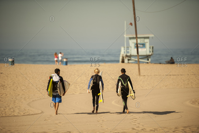 Three young boys walking on Santa Monica and carrying surfboards