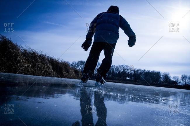 Young boy skating on the frozen lake along Reeds Island, Minnesota, USA