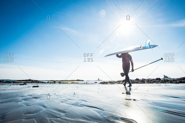 Wide angle view of a man in winter going stand up paddle surfing in Kittery, Maine