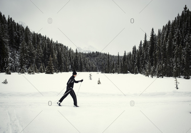 A woman cross country skis in the Canadian rockies in Kananaskis, Alberta