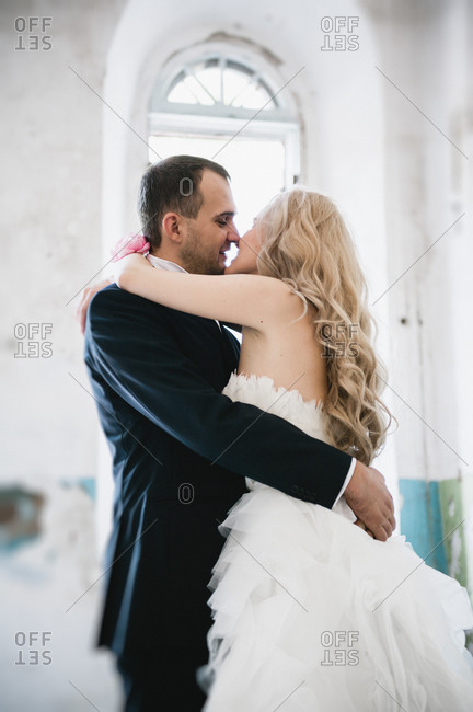 Newlyweds kissing in an abandoned building