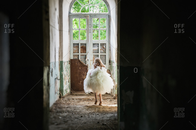 Bride walking towards the exit of an abandoned building