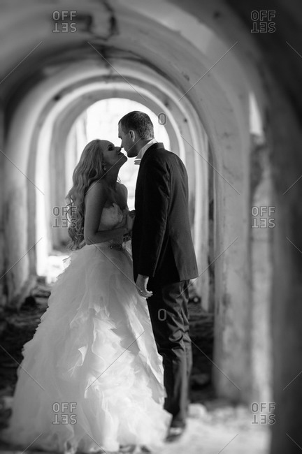 Newlyweds kissing in the hallway of an abandoned building