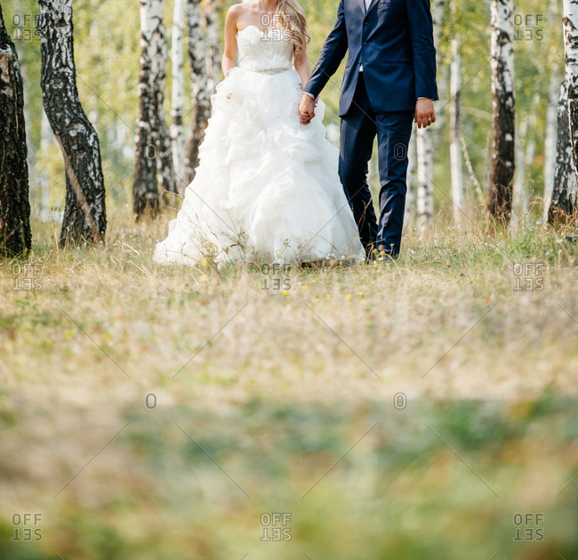 Newlywed couple walking in a birch forest