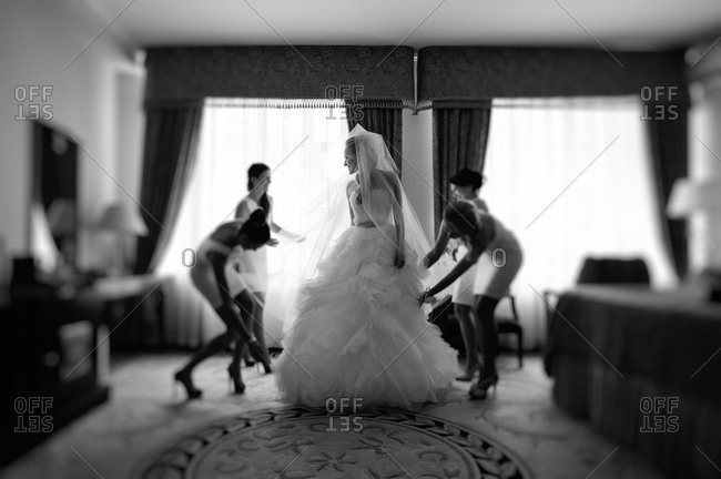Bridesmaids adjusting the bride's dress
