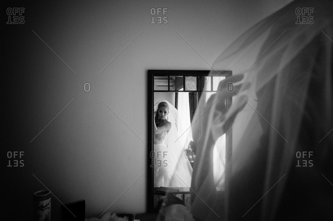 Bride adjusting her veil in front of a mirror