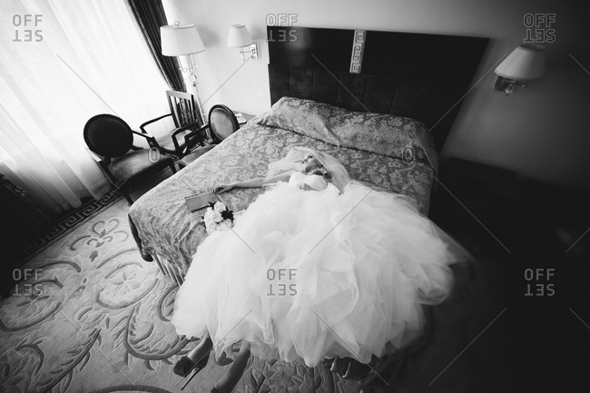 Bride lying on a bed with a book and a bouquet