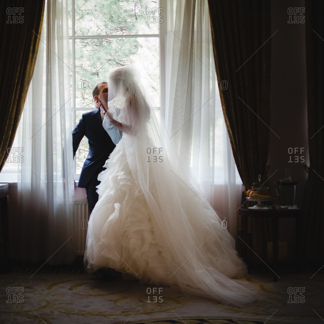Newlywed couple kissing inside a hotel room