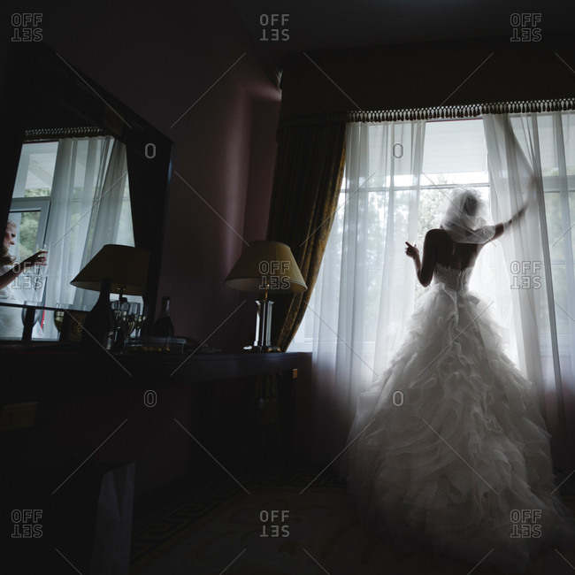 Bride pull the curtains back while standing in front of a window