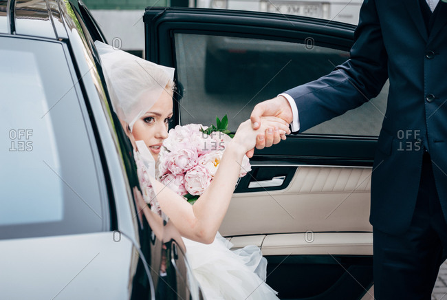 Groom helping bride to step out of a car