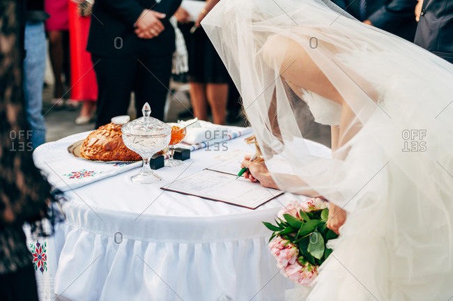 Bride signing a wedding certificate