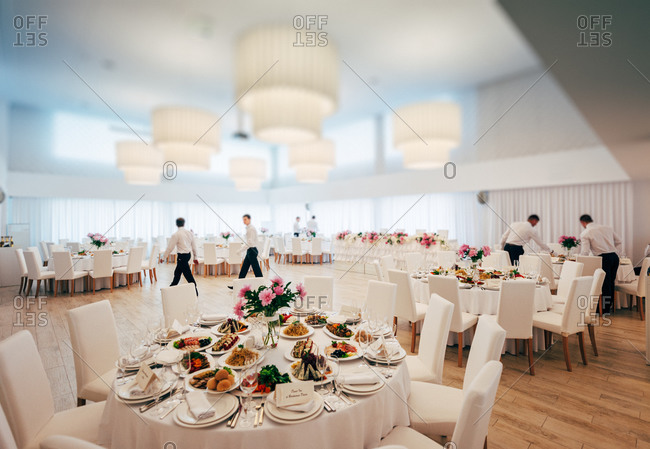 Waiters setting tables for wedding reception