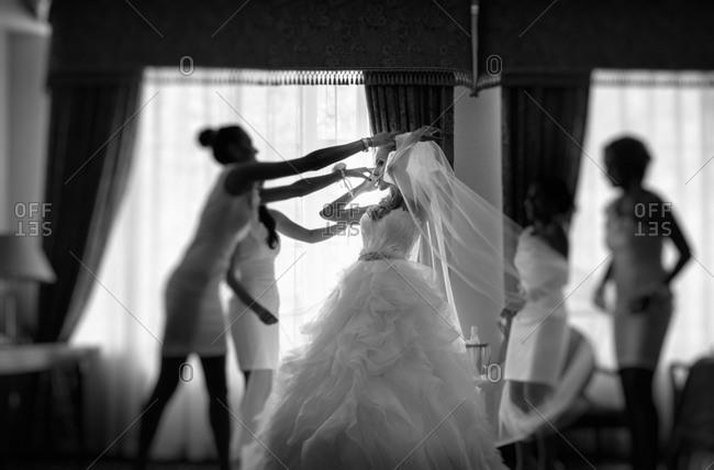 Bridesmaids adjusting the bride's dress