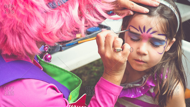 Woman painting a girl's face