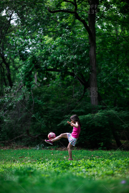 Full length of little girl playing with a soccer ball