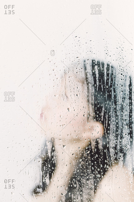 Asian woman behind window pane with water drops