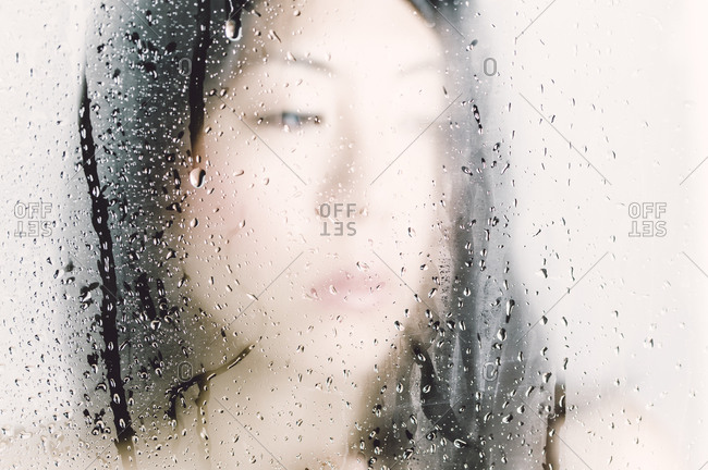 Asian woman looking through a window with water drops