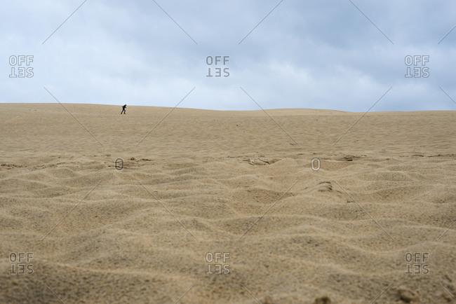 Running boy on a desert like sand dune