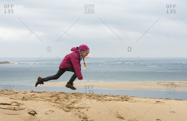Jumping girl on sand dune