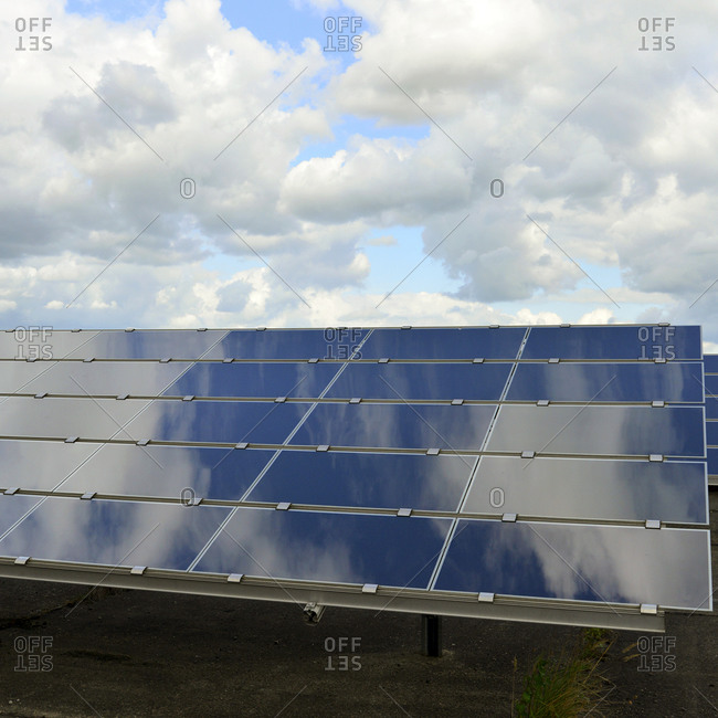 Photoelectric cells of solar power plant with reflections of clouds