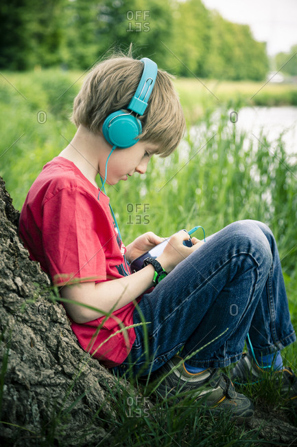 Portrait of boy with smartphone and headphones leaning on tree