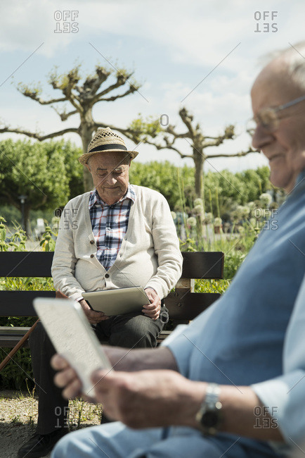 Two old men using tablet computers in the park