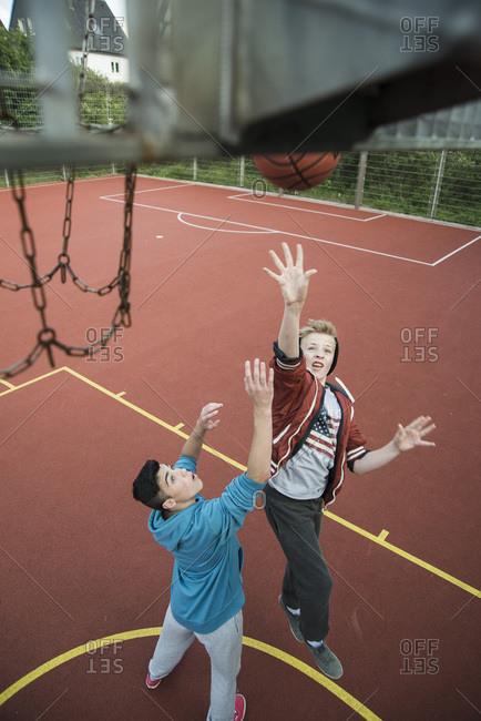 Two boys shooting hoops