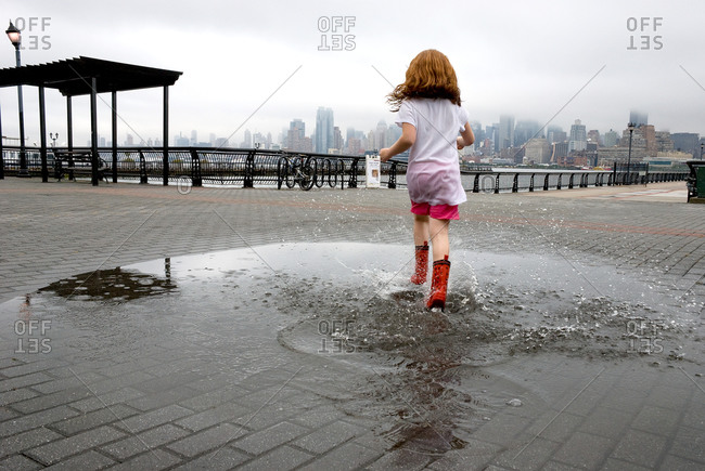 Girl in red boots stepping in a puddle