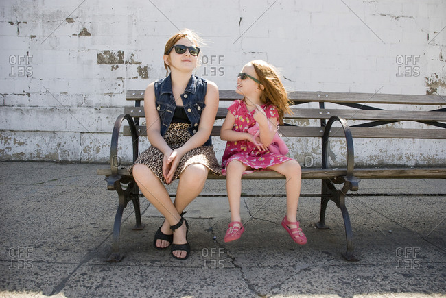 Two girls in sunglasses sitting on bench