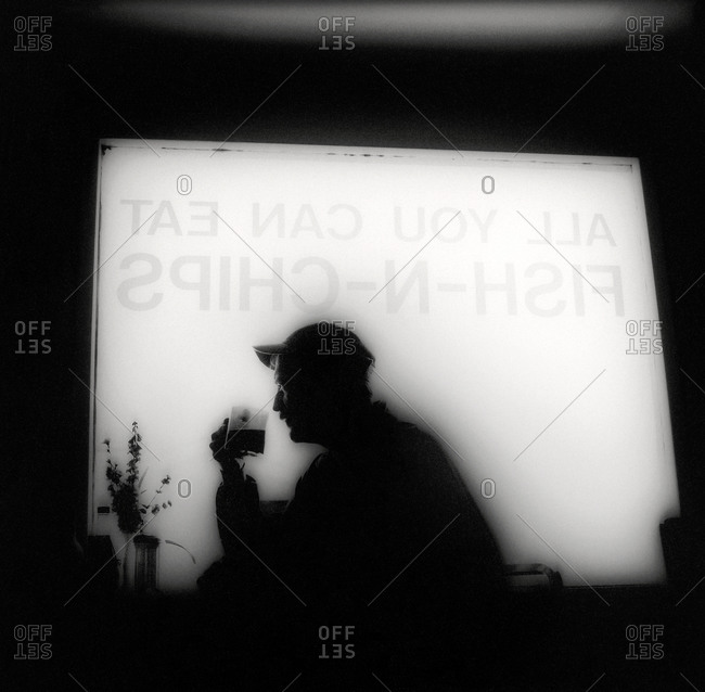 Silhouette of a drinking man