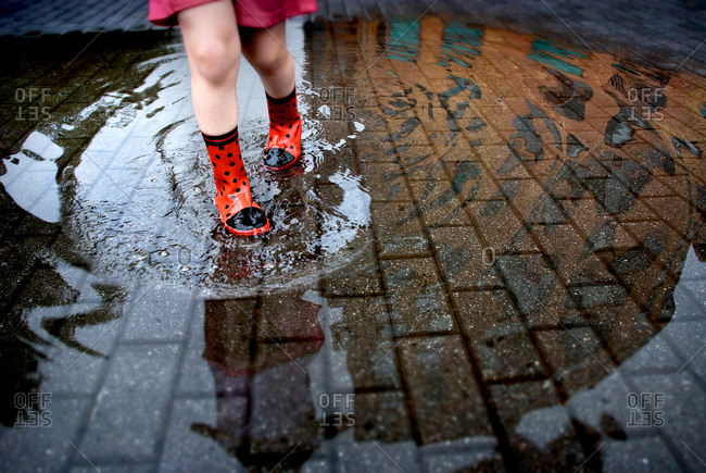 Girl in red boots standing in a puddle