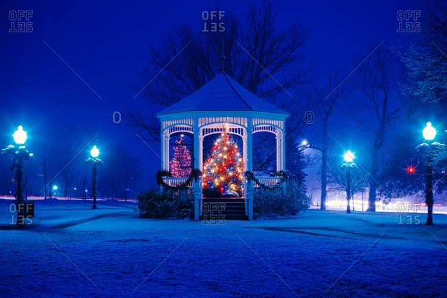Lit up Christmas tree under a gazebo