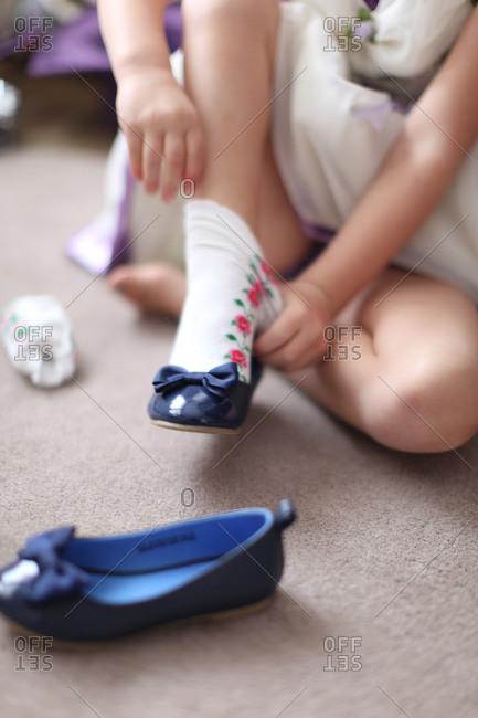 Girl wearing socks and sandal on carpet