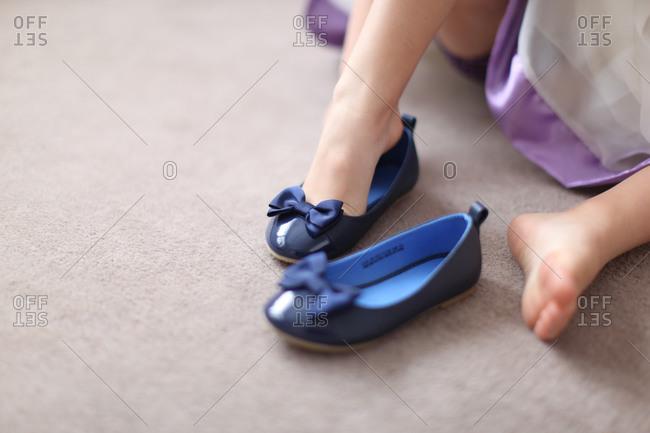 Girl wearing sandal on carpet