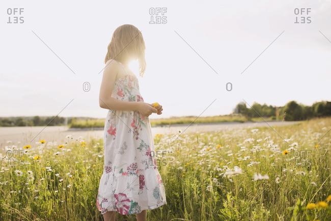 A girl looks dreamily across a field
