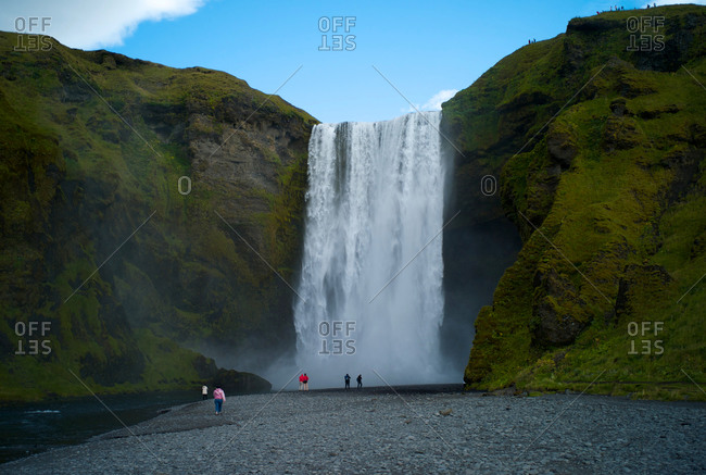 Tourists in front of waterfall in Iceland