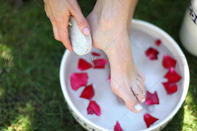Woman taking an outdoor foot bath with rose leaves while exfoliating cracked skin on heel with pumice stone