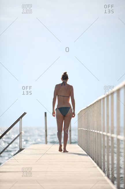 Morning swimmer alone on wooden jetty at Danish beach