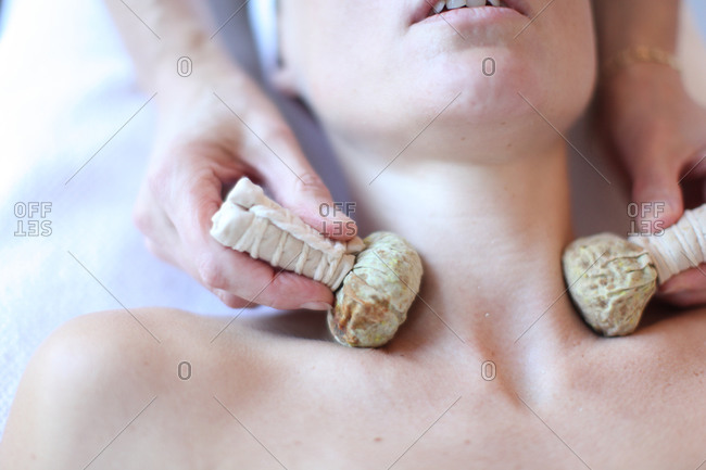 Young woman receiving neck massage with herbal balls