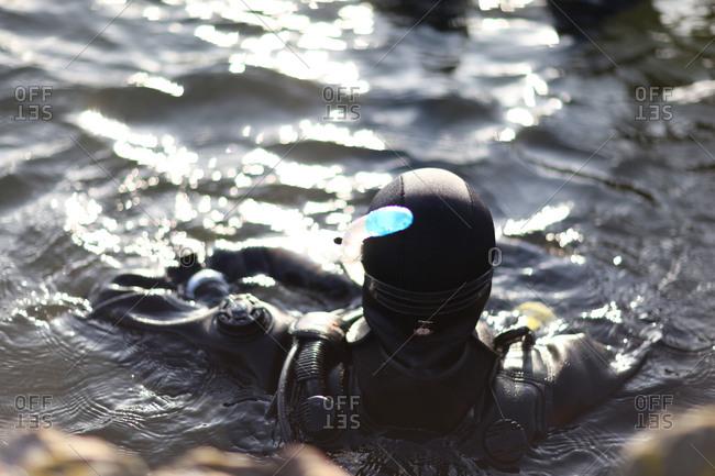 Scuba diver in full gear preparing to enter cold water
