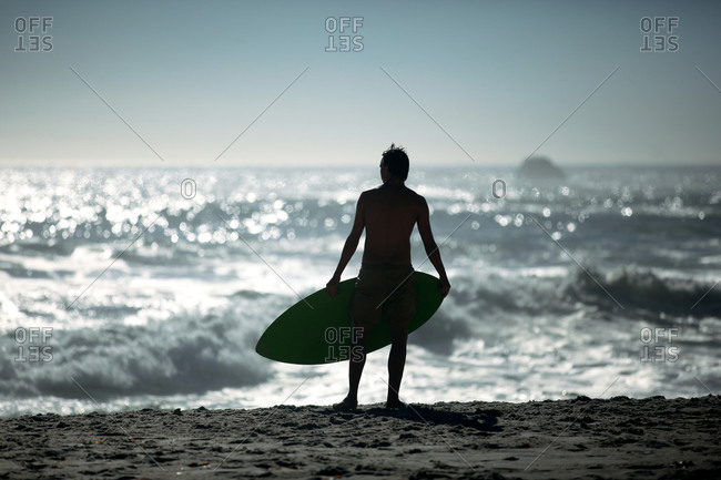 Rear view of young man with surfboard watching sea from beach