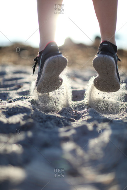 Close up of a woman in sneakers jumping in the sand