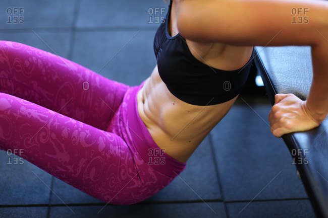 Midsection of woman doing triceps dips health club