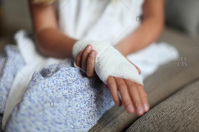 Tanned teenage girl showing bandaged wrist