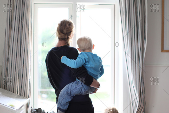 Woman with small boy on arm looking out window in nursery room