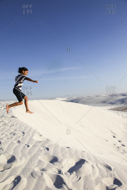 Girl jumping on sand dune in White Sands National Park, New Mexico, USA