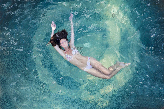 Woman floating in pool in Ojo Caliente, New Mexico, United States