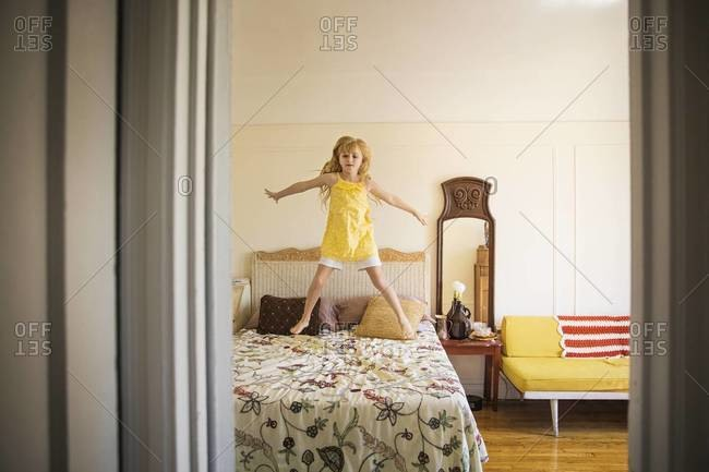 View of little girl jumping on the double bed