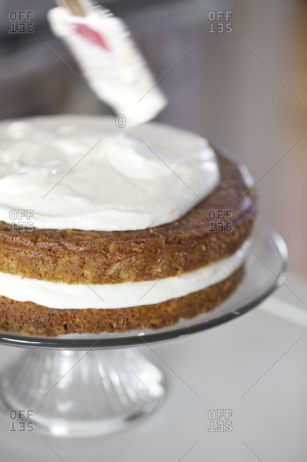 Applying frosting to carrot cake