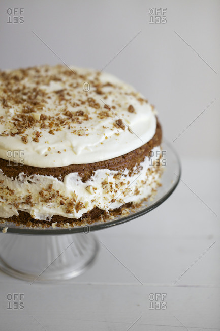 Carrot cake with cream cheese frosting decorated with cake crumbs and walnuts